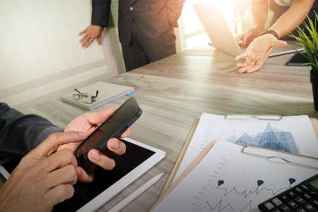 documentos de negocios en la mesa de oficina con teléfono inteligente y el ordenador portátil y el gráfico de negocios con el diagrama de la red social y tres colegas hablando de datos en segundo plano