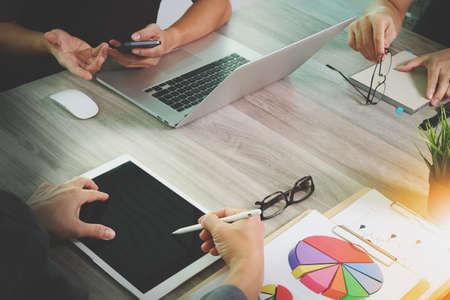 revisando documentos: documentos de negocios en la mesa de oficina con teléfono inteligente y el ordenador portátil y el gráfico de negocios con el diagrama de la red social y tres colegas hablando de datos en segundo plano Foto de archivo