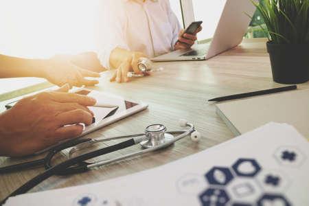 현대 컴퓨터와 디지털 태블릿 의료 개념으로 나무 책상에 자신의 팀과 함께 작업하는 의학 의사 손