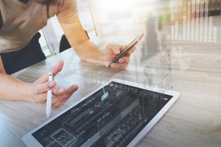 Designer mano che lavora con il computer tablet digitale e smart phone sulla scrivania di legno come responsive web design concept