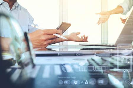 documenti aziendali sul tavolo ufficio con smart phone e computer portatile e grafico di business con diagramma rete sociale e due colleghi che parlano di dati in background Archivio Fotografico