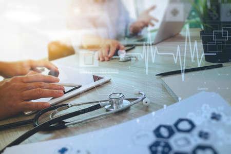ヘルスケア: 医療概念としての木製机の上現代のコンピューターと彼のチームとデジタル医療図デジタル pro タブレット操作医学医師の手の上から見る