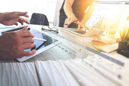 two colleagues interior designer discussing data and digital tablet and computer laptop with sample material and digital design diagram on wooden desk as concept Stock Photo