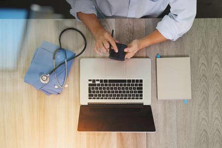 vista dall'alto di Medicina mano medico lavora con il computer moderno e smart phone sulla scrivania di legno come concetto medico