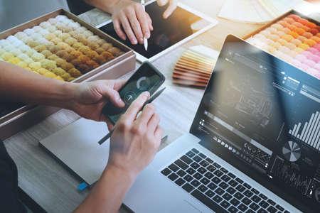 arquitecto: vista desde arriba de dos colegas diseñadores de interiores en discusiones con el diagrama de datos de diseño en la nueva pantalla de la computadora portátil moderna y el teléfono inteligente con material de muestra en el escritorio de madera como concepto
