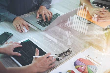 hoja de calculo: documentos de negocios en la mesa de oficina con teléfono inteligente y el ordenador portátil y el gráfico de negocios con el diagrama de la red social y tres colegas hablando de datos en segundo plano Foto de archivo