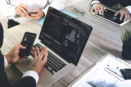 red informatica: documentos de negocios en la mesa de oficina con teléfono inteligente y el ordenador portátil y el gráfico de negocios con el diagrama de la red social y tres colegas hablando de datos en segundo plano Foto de archivo