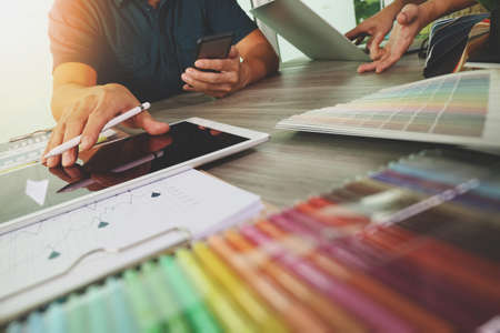 dos colegas, entre diseñador de discutir los datos y la tableta digital y ordenador portátil con material de muestra en el escritorio de madera como concepto