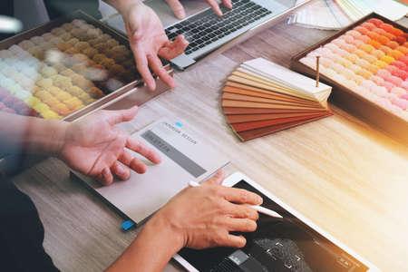 bovenaanzicht van twee collega's interieurarchitecten bespreken data met nieuwe moderne computer laptop en pro digitale tablet en digitaal ontwerp diagram op het scherm met monstermateriaal op houten bureau als concept Stockfoto
