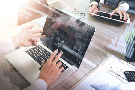 business documents on office table with smart phone and laptop computer and graph business with social network diagram and two colleagues discussing data in the background