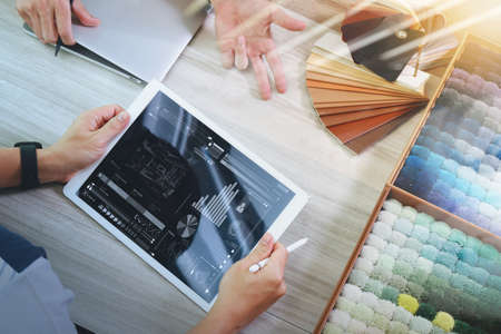 sample: top view of two colleagues interior designers discussing data with digital tablet and new modern computer laptop with sample material on wooden desk as concept
