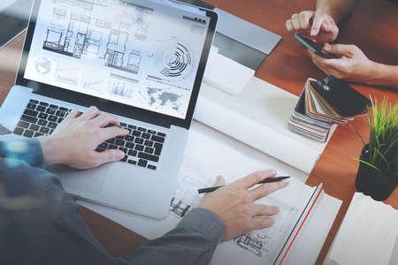 Vista dall'alto di due colleghi interior designer che parlano di dati con il nuovo computer portatile moderno e tavoletta digitale pro con materiale campione sulla scrivania in legno come concetto Archivio Fotografico