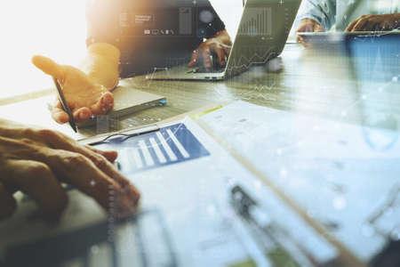 3 人の同僚間の概念としてデザイナーの議論データとデジタル タブレットとコンピューター ラップトップ ビジネス文書とデジタル設計図木製の机の