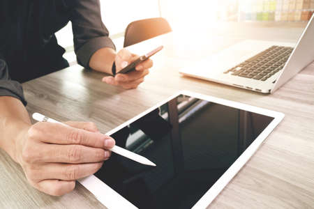 概念として木製の机の上の空白の画面デジタル タブレットとスマート フォンとラップトップ コンピューターの作業のウェブサイトのデザイナー