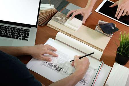 de colores: vista desde arriba de dos colegas diseñadores de interiores en discusiones datos con la pantalla en blanco nueva computadora portátil moderna y la tableta digital profesional con material de muestra en el escritorio de madera como concepto