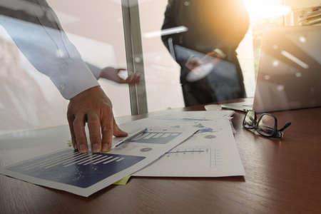 desarrollo económico: dos colegas hablando de datos con el nuevo ordenador portátil moderno y tableta digital profesional con efecto de capa estrategia de negocio digital en el escritorio de madera como concepto