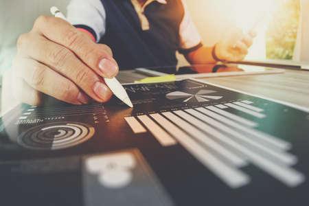 documentos de negocios en la mesa de oficina con teléfono inteligente y la tableta digital y gráfico de negocio con el diagrama de la red social y el hombre que trabajan en segundo plano Foto de archivo