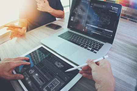 two colleagues Website designer working digital tablet and computer laptop with smart phone and digital design diagram on wooden desk as concept