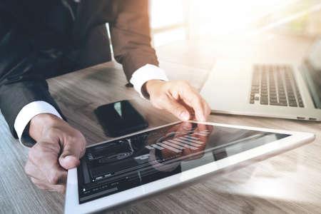 デジタル タブレット コンピューターとスマート携帯電話とラップトップ コンピューター デジタル ビジネス戦略レイヤー効果概念として木製の机の 写真素材