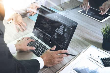 documenti aziendali sul tavolo ufficio con smart phone e computer portatile e di business grafico con diagramma di rete sociale e tre colleghi che parlano di dati in background Archivio Fotografico