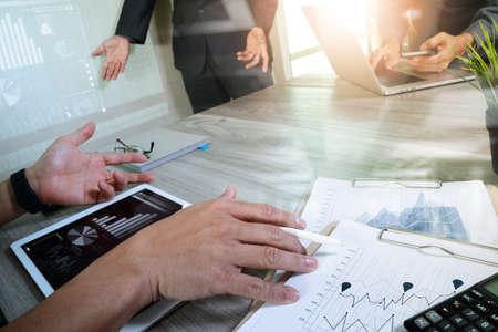 documentos de negocios en la mesa de oficina con teléfono inteligente y el ordenador portátil y el negocio gráfico digital con diagrama de red social y tres colegas hablando de datos en segundo plano