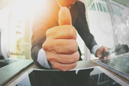 close up of businessman giving thumbs up in his office as concept