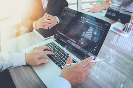 recursos financieros: documentos de negocios en la mesa de oficina con tel�fono inteligente y el ordenador port�til y el gr�fico de negocios con el diagrama de la red social y tres colegas hablando de datos en segundo plano Foto de archivo