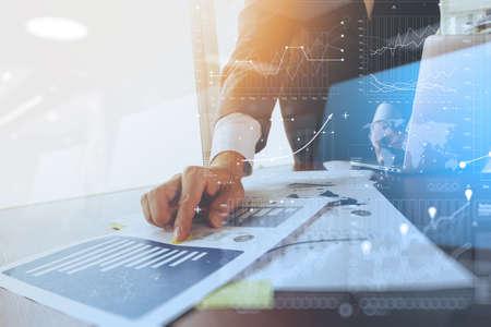documenti aziendali sul tavolo ufficio con il computer portatile e di business grafico con diagramma di rete sociale e l'uomo che operano nel backgroun