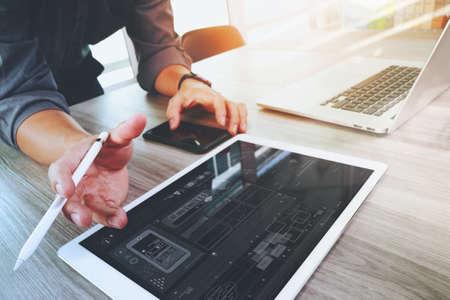 Website ontwerper die digitale tablet en computer laptop en digitale diagram op houten bureau als concept Stockfoto