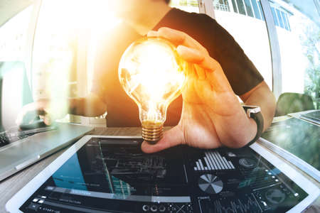 designer hand showing creative business strategy with light bulb as concept