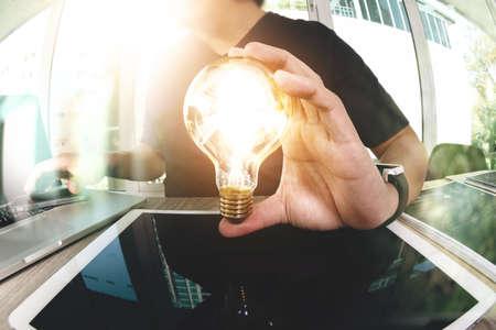 デザイナーの手を示す概念として電球に創造的なビジネス戦略