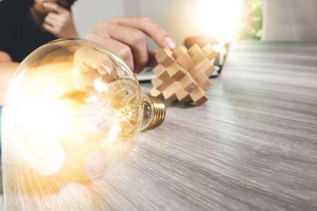 main créatrice montrant bois puzzle et ampoule avec un ordinateur portable et ordinateur tablette comme concept