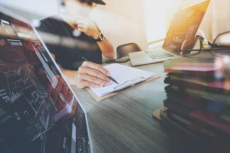 デジタル タブレットとスマート フォンとデジタル設計図のコンセプトとして木製の机の上の本のスタックとコンピューター ノート パソコンの作業