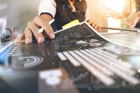 economic: business documents on office table with smart phone and digital tablet and graph business with social network diagram and man working in the background Stock Photo