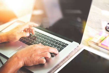 web sites: Designer hand working with laptop computer on wooden desk as responsive web design concept