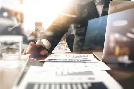 zakelijke documenten op kantoor tafel met slimme telefoon en leeg scherm laptop computer en grafiek zakelijke diagram en twee collega's bespreken op de achtergrond gegevens