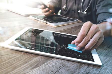 医療技術コンセプト。医師手カルテ インターフェイス、太陽フレア効果写真と現代デジタル タブレットとラップトップ コンピューターで作業 写真素材