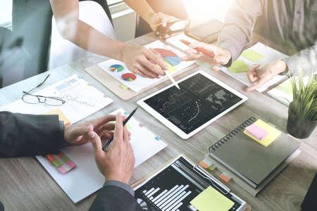スマート携帯電話およびラップトップ コンピューターとグラフのビジネス ソーシャル ネットワーク図と背景のデータを議論する 3 人の同僚のオフ