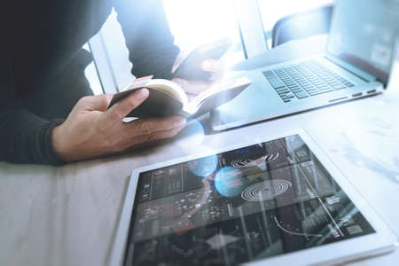finance manager: Businessman hand holding book and digital tablet.Photo finance manager working new Investment project office.Using new technology device.Graphic icons.Strategy business stock exchanges