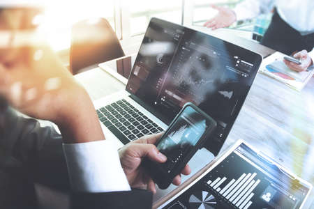 Business team meeting present. Photo professional investor working with new startup project. Finance managers meeting.Digital tablet laptop computer design smart phone using, Sun flare effect 版權商用圖片