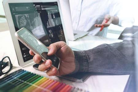 데이터 및 디지털 태블릿을 논의하는 두 동료 웹 디자이너 스마트 전화 및 디자인 다이어그램 개념으로 대리석 책상에 디지털 태블릿 및 컴퓨터 노트 스톡 콘텐츠
