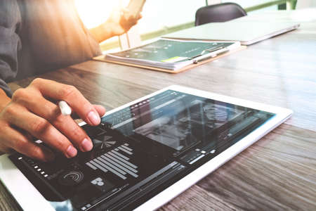 finance manager: Businessman hand touching digital tablet.Photo finance manager working new Investment project office.Using new technology device.Graphic icons.Strategy business stock exchanges interface layer effect, Horizontal
