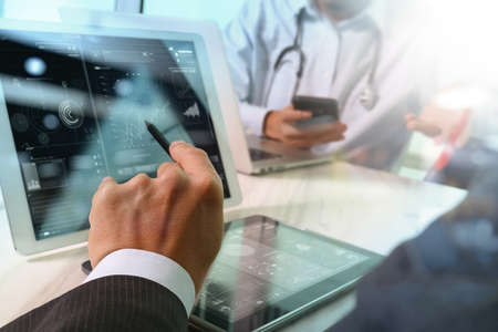 Medical technology network team concept. Doctor hand working with smart phone modern digital tablet and laptop computer with graphics  chart interface, Sun flare effect photo