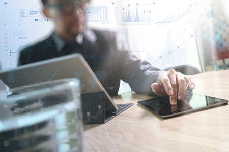 finance manager: Businessman hand touching digital tablet.Photo finance manager working new Investment project office.Using new technology device.Graphic icons.Strategy business stock exchanges interface layer effect Stock Photo