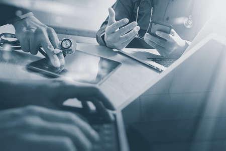 Medical technology network team meeting concept. Doctor hand working smart phone modern digital tablet dock keyboard. laptop computer graphics chart interface, sun flare effect, black white