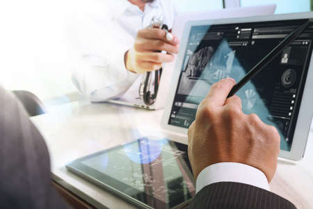 Medical technology network team meeting concept. Doctor hand working with smart phone modern digital tablet and laptop computer with graphics chart interface, double exposure effect photo