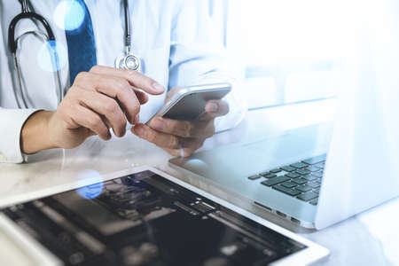 Medical technology concept. Doctor hand working with modern digital tablet and laptop computer with medical chart interface, Sun flare effect photo Stock Photo