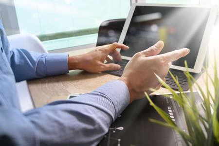 Businessman hand working concept. Documents finance graphic chart. Digital tablet keyboard dock screen computer design smart phone using. Eyeglass on marble desk. Sun beams effect