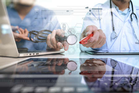 Medical technology network team meeting concept. Doctor hand working with smart phone modern digital tablet and laptop computer with graphics chart interface, Sun flare effect photo Reklamní fotografie