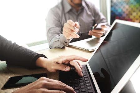 데이터 및 디지털 태블릿 도킹을 논의하는 두 동료 웹 디자이너 키보드 및 컴퓨터 노트북 스마트 전화 및 디자인 다이어그램 대리석 책상, 태양 빛 효 스톡 콘텐츠